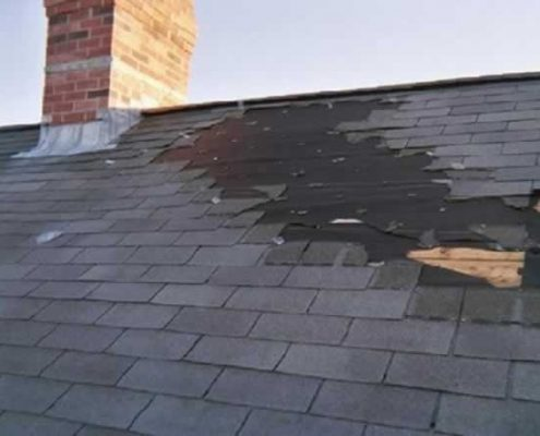 A Kittery Maine house with brick chimney and entire layer of asphalt shingles ripped right off the roof in a wind storm